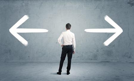 confundido: Un hombre de negocios de duda, tener que shoose entre dos opciones diferentes indicadas por las flechas que apuntan en dirección opuesta concepto Foto de archivo