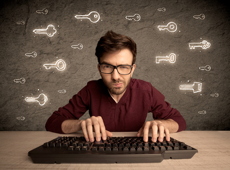 internet keyboard: A young internet geek working online, hacking login passwords of social media users concept with glowing drawn keys on the wall