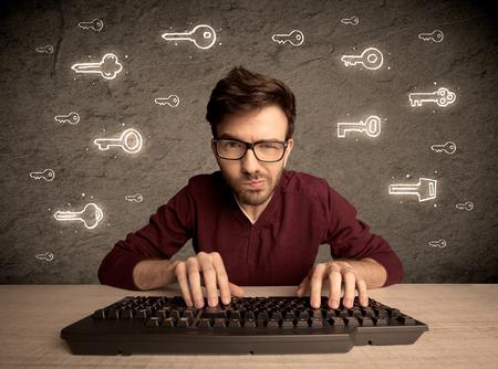 seguridad en el trabajo: Un joven friki internet trabajar en línea, la piratería de inicio de sesión contraseñas de los usuarios de medios sociales concepto con brillantes teclas dibujadas en la pared