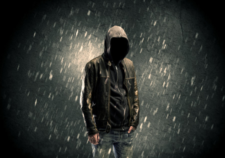 bad guy: A faceless misterious man in hoodie and leather jacket standing in the dark with a visible silhouette concept