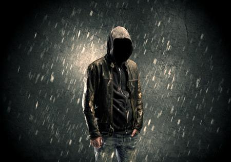 Een anonieme mysterieuze man in hoodie en leren jack staat in het donker met een zichtbare silhouet begrip Stockfoto