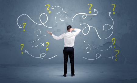 Un vendedor de duda no puede encontrar la solución al problema de concepto con las flechas alineadas con curvas y signos de interrogación dibujado en la pared urbana