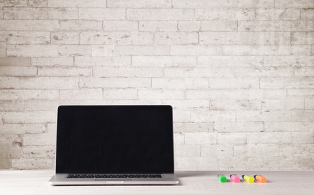 Een open laptop op een bureau met bloem, koffie, boeken in de voorkant van witte bakstenen muur, achtergrond, concept