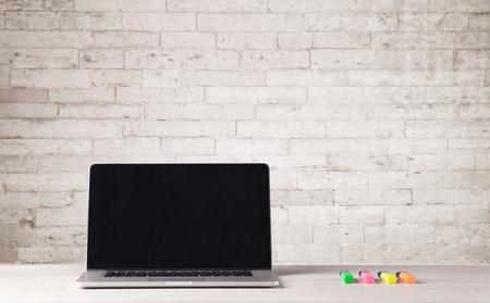 Egy nyitott laptop egy íróasztal virág, kávé, könyvek előtt fehér téglafal háttér, fogalom