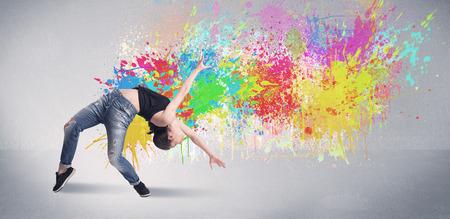 Een funky hedendaagse hip hop danser in de voorkant van grijze achtergrond met kleurrijke heldere verf splatter-concept