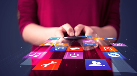 network connections: Woman holding smart phone with colorful application icons comming out