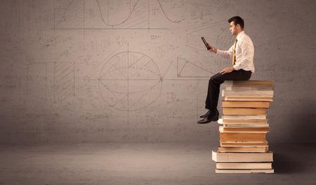 diligente: Un hombre de negocios serio con la tableta en la mano en el juego que se sienta en una pila de libros gigantes delante de una pared de color marrón grisáceo incluyendo dibujadas líneas, ángulos, números, círculos y curvas.