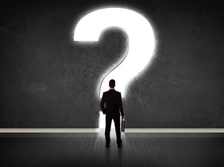 confundido: Hombre de negocios que mira la pared con un concepto de signo de interrogación brillante Foto de archivo