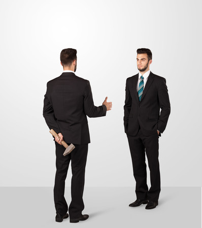 unethical: Two opposing businessman shake hands, one of them hiding a weapon behind his back