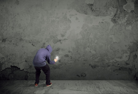 grafitis: Pintor urbano joven que comienza a dibujar graffiti en la pared