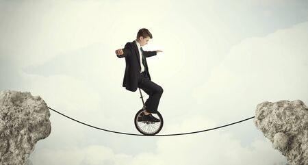 mono: Brave business man riding an mono cycle between cliffs concept