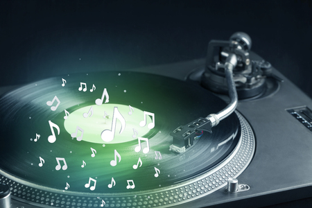 audiophile: Turntable playing music with audio notes glowing concept on background Stock Photo