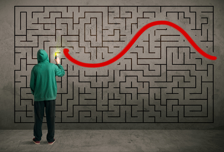 painter: Young urban painter drawing a red solution line on the wall maze Stock Photo