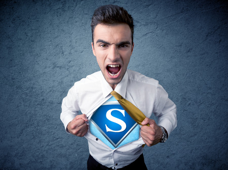 ripping shirt: Businessman ripping off his shirt with superhero sign on his chest concept on background