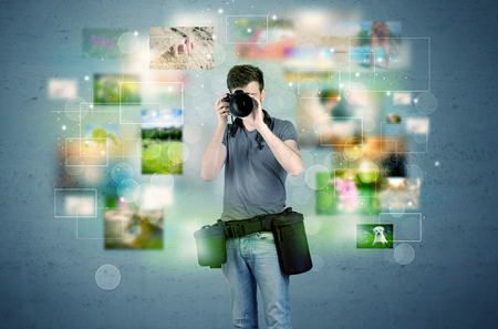 amateur: Un joven aficionado a la fotografía con el equipo de cámara profesional que toma el cuadro en frente de la pared azul lleno de fotografías descoloridas y brillantes luces de concepto