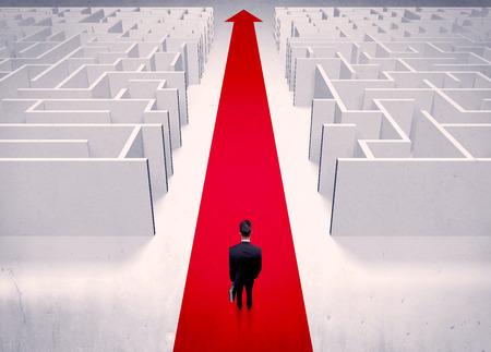 laberinto: Un elegante hombre de negocios de adultos de pie sobre una alfombra roja flecha hacia adelante a trav�s de una calle con laberinto en dos lados concepto