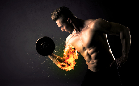 male bodybuilder: Bodybuilder athlete lifting weight with fire explode arm concept on background