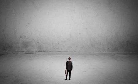 Een uiterst kleine elegante zakenman die zich in grote lege stedelijke ruimte met concrete muren en grijs concept bevindt als achtergrond Stockfoto