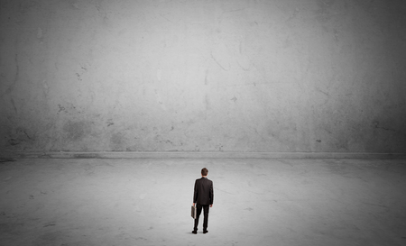 A tiny elegant businessman standing in large empty urban space with concrete walls and grey background concept