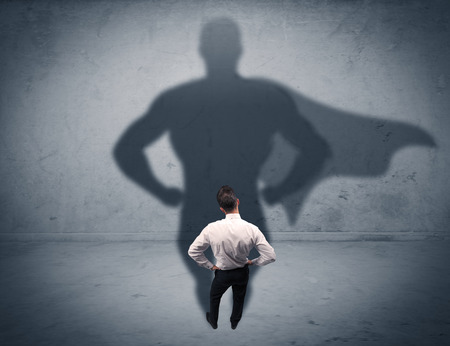 A confident young elegant salesman with briefcase facing a wall, looking at his super hero shadow concept Stock Photo
