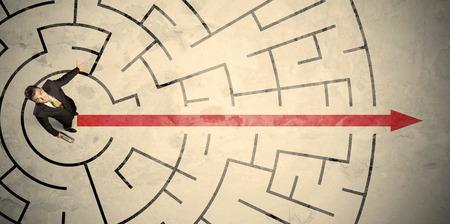 Üzleti ember állt a közepén egy kör alakú labirintus piros nyíl