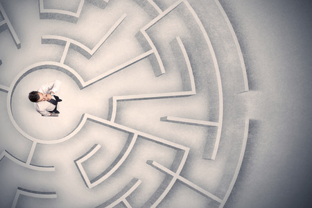 confused: Confused business man trapped in a circular maze Stock Photo
