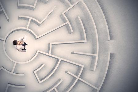 confundido: Hombre de negocios confuso atrapado en un laberinto circular
