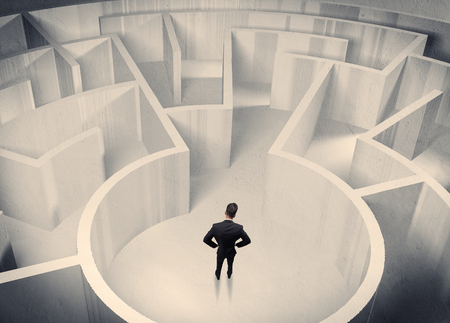 confused: A confused businessman standing in the center of a maze surrounded with walls of the labyrinth