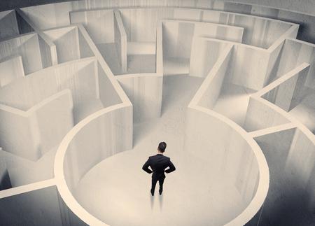 confundido: Un hombre de negocios de confusión de pie en el centro de un laberinto rodeado de paredes del laberinto