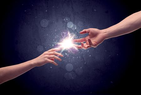 paz: Duas mãos masculinas atingindo em direção ao outro, quase tocando com os dedos, faísca iluminação no conceito do fundo da galáxia