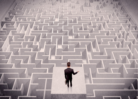 confusing: A confused businessman thinking while standing on a square platform above a detailed maze
