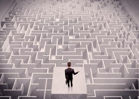 laberinto: Un hombre de negocios confuso pensando mientras est� de pie sobre una plataforma cuadrada por encima de un laberinto detallada