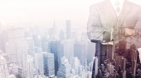 business men: Business man standing on roof with city view in the background Stock Photo