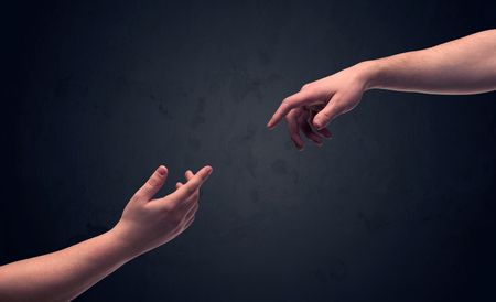 people helping people: Two male hands reaching out to one another, almost touching, in front of dark clear empty background wall concept