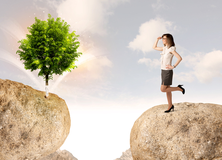 bridging the gaps: Businesswoman standing on the edge of rock mountain with a tree on the other side