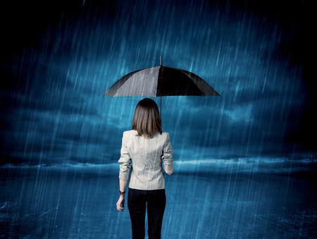 caja fuerte: Mujer de negocios de pie en la lluvia con un concepto paraguas en el fondo