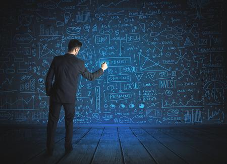 schemes: Businessman drawing business schemes on glass wall