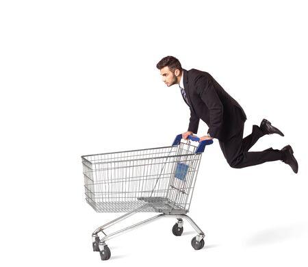 push people: Businessman pushing a shopping cart on isolated background