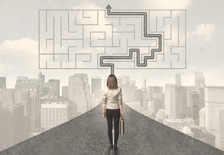 Business woman looking at road with maze and solution concept Standard-Bild