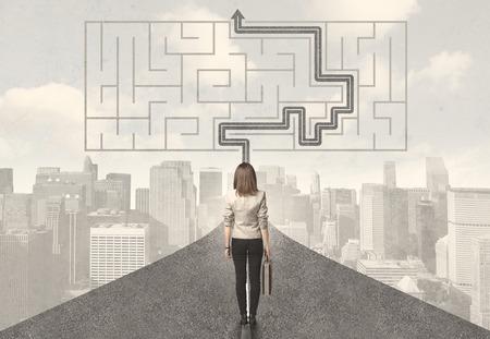 confundido: Mujer de negocios mirando a la carretera con laberinto y concepto de la solución