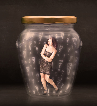 locked up: Business woman trapped in jar with exclamation marks concept on bakcground