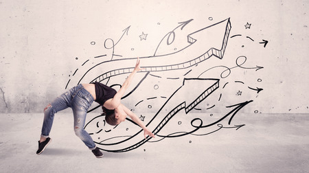 contemporary dance: A beautiful young hip hop dancer dancing contemporary street dance in front of urban grey wall background with lines and arrows concept Stock Photo