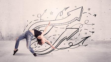 danza contemporanea: Una joven hermosa bailarina de hip hop bailando la danza contemporánea calle delante de fondo gris de la pared urbana con líneas y flechas concepto