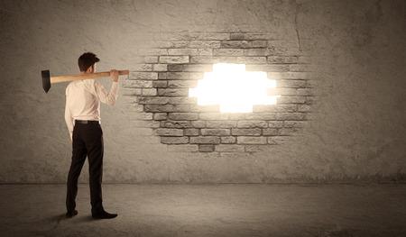 Üzletember üti tégla szutykos fal kalapáccsal és megnyitása egy lyuk