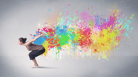 contemporary dance: A funky contemporary hip hop dancer dancing in front of grey background with colorful bright paint splatter concept