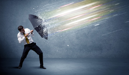 estado del tiempo: Business man defending light beams with umbrella concept on background