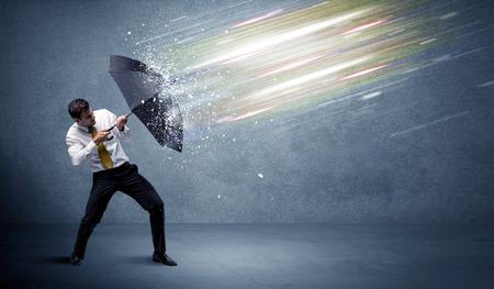 concepto: Hombre de negocios que la defensa de los haces de luz con el concepto paraguas en el fondo