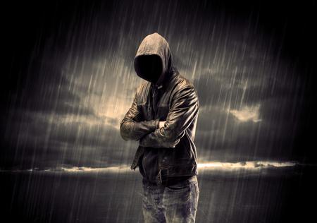 ladron: Un ladr�n sin rostro irreconocible en hoodie de pie en medio de la noche bajo la lluvia frente a concepto de paisaje Foto de archivo