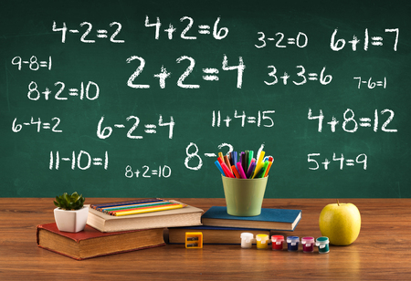 manzana verde: Volviendo al concepto de escuela con pizarra llena de números y escritorio estudiante ocupado