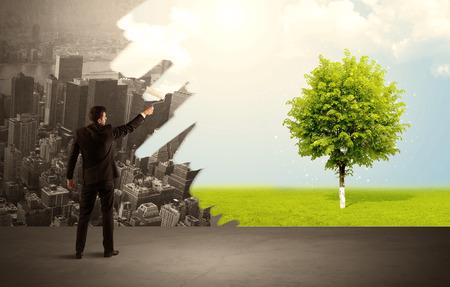 Üzletember, elegáns öltöny aki háttal állt, kezében egy görgő és átalakítja a szürke városi táj a zöld fa, élénk természet környezet fogalma